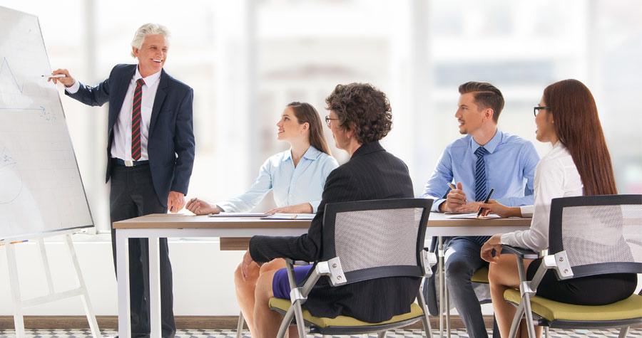 homem fazendo uma apresentaçã pra pessoas sentadas em uma reunião