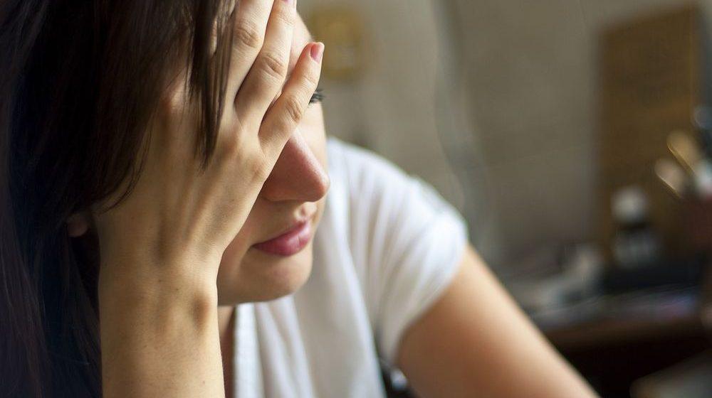 imagem de uma mulher de cabe;a baixa e mão na cabe;a